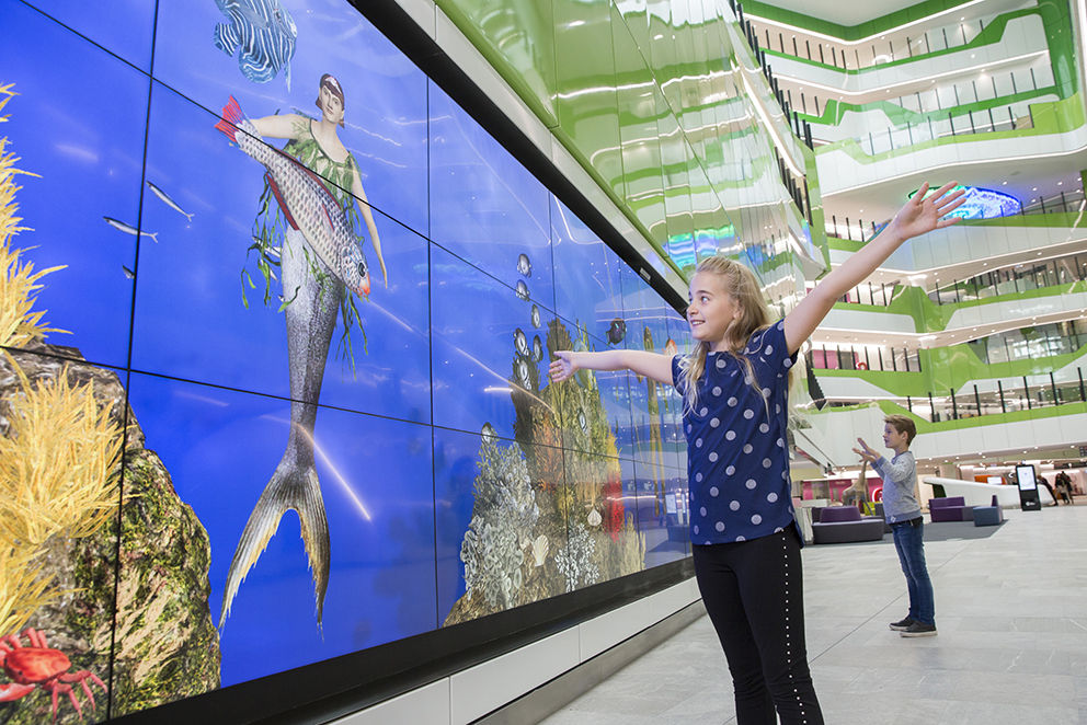 Children play in front of PCH's interactive digital wall